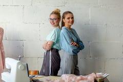 Довольно молодой женский дизайнер 2 смотря камеру в шить мастерской стоковое изображение