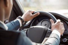 Дозор молодого водителя бизнесмена нося сидя внутри руля удерживания автомобиля управляя взглядом конца-вверх задним стоковые фотографии rf
