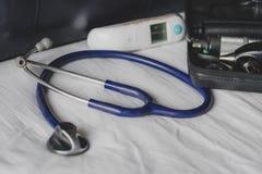 Доктора кладут в мешки на клинике - стетоскоп, otoscope и термометр показа стоковое фото rf