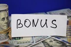 100 долларовых банкнот переплетенных в трубу и связанных со строкой Надпись бонуса стоковые фотографии rf