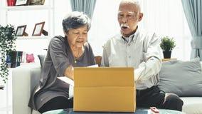Доставка, почта, доставка и концепция людей - старший человек и коробка пакета отверстия женщины дома, видеоматериал