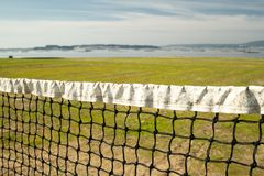Достигшая возраста сеть волейбола пляжа с предпосылкой моря стоковые фото