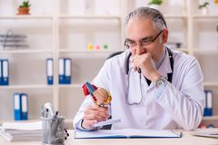 Достигший возраста мужской кардиолог доктора с моделью сердца стоковое фото
