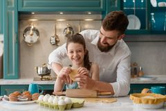 Дочь и папа делая печенья стоковая фотография