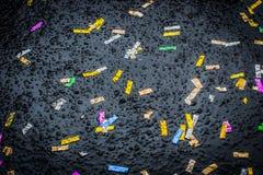 在湿沥青背景的Ð ¡ olorful五彩纸屑 免版税库存照片