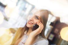 Цoman opowiada z somebody telefonem komórkowym i uśmiechy, jest wśrodku przyglądający przez ampuł wi i cukiernianego out Zdjęcia Stock