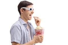 Ð-… oungman som bär exponeringsglas 3D och äter popcorn Arkivfoto