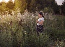 Уoungmeisje op de achtergrond van wildflowers Stock Afbeeldingen