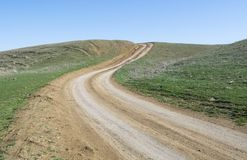 Rural Road. Сountry road in the field, leading to the mountain top Royalty Free Stock Photo