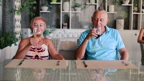 Ð ¡ ouple των ανθρώπων που πίνουν τη συνεδρίαση κρασιού σε έναν πίνακα φιλμ μικρού μήκους