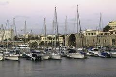 Ð ¡ ozy小游艇船坞在伊拉克利翁的心脏历史大厦背景背景的  免版税库存照片