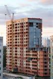 Ð-¡ rane och byggnad under konstruktion av gul och röd tegelsten Arkivfoto