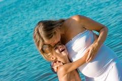 Ð regnant Mutter, die ihren Sohn küßt Stockbild