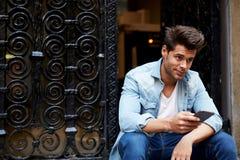 Ð ¡ ropped使用他的手机的一个时兴的人的射击在城市布局 库存图片