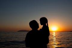ШSilhouette женщины и маленькой девочки, наслаждаясь и ослабляя, на th Стоковые Изображения RF