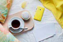 Ð-¡ upp av kaffe och mobiltelefonen i en säng med tomma kort Royaltyfri Fotografi
