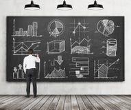 Ð'usinessman lub uczeń finanse lub zarządzanie programujemy rysujemy niektóre wykresy na czarnym chalkboard lub mapy Tyły rywaliz Obrazy Royalty Free