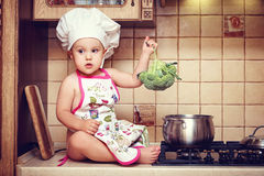 Ð-¡ ute behandla som ett barn lite sitter på ett köksbord och innehavbroccoli arkivbilder