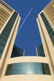 Самолет летает против голубого неба над современным городом Нижний взгляд стоковое фото
