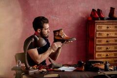 Сапожник смотря ботинки с дефектами стоковое фото rf
