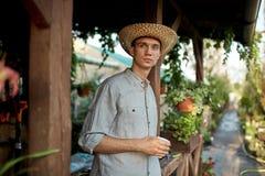 Садовник Гай в соломенной шляпе стоит с пластиковым стеклом в его руке рядом с деревянной верандой в чудесном питомнике стоковое фото rf