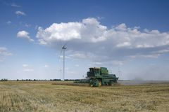 Сборы зернокомбайна на поле Ветрогенераторы на заднем плане стоковая фотография rf
