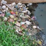 Свалка мусора в канале воды из городского водопровода, много отбросе стоковая фотография