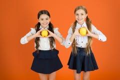 Свеже и вкусно Небольшие девушки есть естественную еду витамина Милые школьницы держа яблоки Ребята школьного возраста со здоровы стоковое изображение