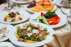 Свежий салат смешивания с ветчиной, фета и манго на белой плите китайская таблица типа установки стоковая фотография