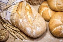 Свежий хлеб и пшеница на деревенской предпосылке стоковое фото