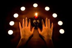 Свечи и женские руки с острыми ногтями на деревянной поверхности Divination и колдовство, низкий ключ стоковая фотография rf