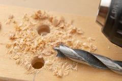 Сверлить отверстие в древесине Деревянные сверло и переклейка в мастерской плотничества стоковые фотографии rf