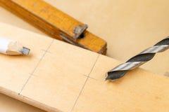 Сверлить отверстие в древесине Деревянные сверло и переклейка в мастерской плотничества стоковое изображение rf