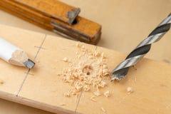 Сверлить отверстие в древесине Деревянные сверло и переклейка в мастерской плотничества стоковое фото rf