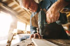 Сверлить отверстие на деревянной планке стоковое изображение