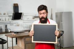 Секретные подсказки информация полезная Стойка рисбермы бородатого хипстера человека красная в кухне Мебельный магазин кухни Моты стоковая фотография