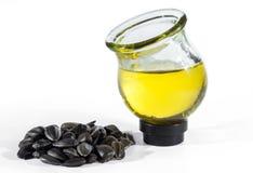 Семена подсолнуха и подсолнечное масло в круглом стеклянном опарнике изолированном на белом b стоковые изображения rf