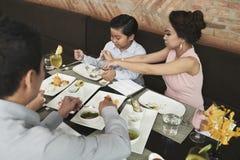 Семья есть обедающий на таблице стоковое изображение