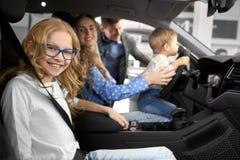 Семья представляя в кабине автомобиля нового автомобиля стоковое изображение rf