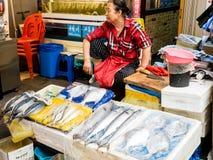 Сеул, Южная Корея - 26-ое июня 2017: Продавец рыб женщины ждет покупателей на рынке Gwangjang в Сеуле стоковые изображения