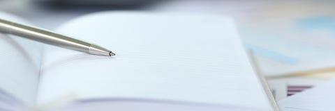 Серебряная ручка лежа на раскрытом листе тетради стоковое изображение rf
