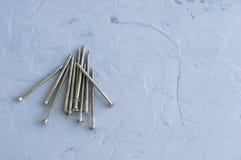 Серебряные винты металла для стен На серой конкретной предпосылке Конец-вверх стоковые фото