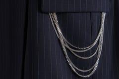 Серебряные цепи на классическом голубом striped костюме вися вне из кармана стоковые фото