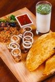 середина кухни восточная Pasties, kebabs, pilaf, ayran на деревянной разделочной доске стоковая фотография rf