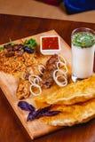 середина кухни восточная Pasties, kebabs, pilaf, ayran на деревянной разделочной доске стоковые фотографии rf