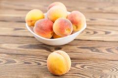 Серия свежих всех зрелых персиков в белом керамическом шаре и одном персике отдельно стоковое изображение