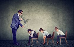 Сердитый босс кричащий в мегафоне давая заказы грустный смотреть вниз с женских работников стоковая фотография rf