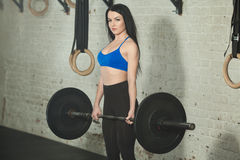 Серьезная спортивная девушка. Beautiful young girl in great shape with a barbell in her arms in the gym Stock Photography