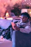 Серьезный парень выпивая травяной чай пока играющ игру на планшете стоковые изображения