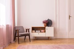 Серое винтажное кресло рядом с деревянным шкафом с книгами и вереском в баке, реальном фото с космосом экземпляра на пустой стене стоковое фото